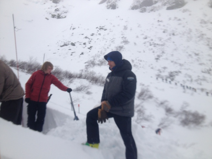 EMS Guide Keith Moon coaches snowpack observations while a large group enters the ravine below